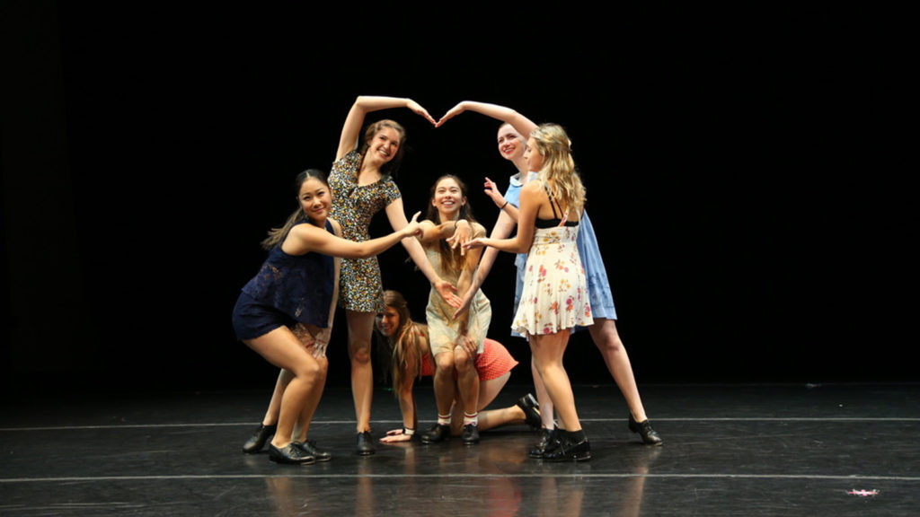 Dancers make a heart with their bodies on stage