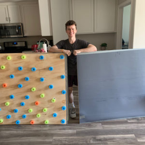 Eli Alford posing with the supplemental floors he built for dance class.
